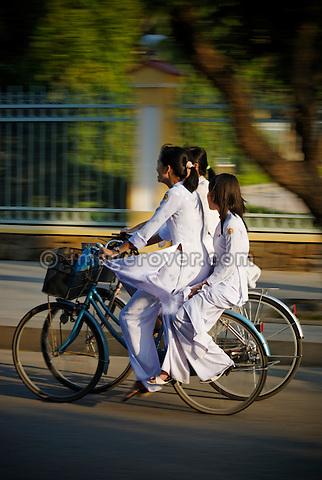 Asia, Vietnam, Hue. Girls in traditional vietnamese white dresses returning from school.