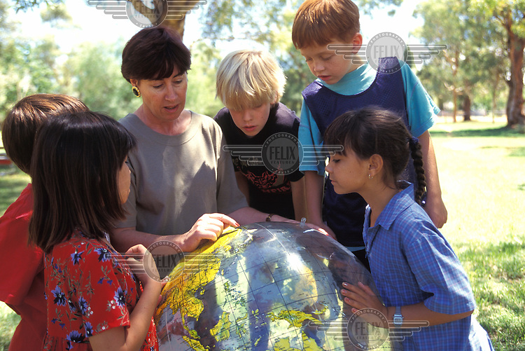 Eight year old Alexis Abala (R) studies an inflatable globe with a teacher and classmates in a geography lesson at Ross Park school.  Alexis is half Aboriginal.