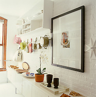 In the kitchen a rank of simple cabinets from Ikea is ranged along one wall providing ample storage and shelving while pots and pans hang below an open shelf containing a collection of white crockery