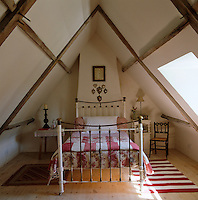 A wrough-iron bed covered with red and white quilts takes centre stage in this attic bedroom