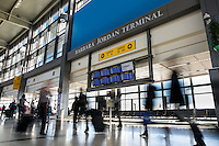 Travelers rush past the flight information display monitors in the terminal at Austin's ABIA Airport