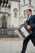 A legal clerk carries case documents.  The Royal Courts of Justice, London.