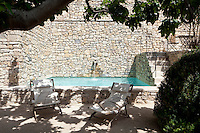 This cool outdoor swimming pool is enclosed by walls of natural colour stone with a terrace shaded by a tall tree
