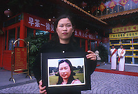 Gou Xiao holds a picture showing her before her eye widening operation in Shenzhen, China. As the Chinese population grows richer more and people are turning to cosmetic surgeons for nose, eye and breast jobs....PHOTO BY SINOPIX