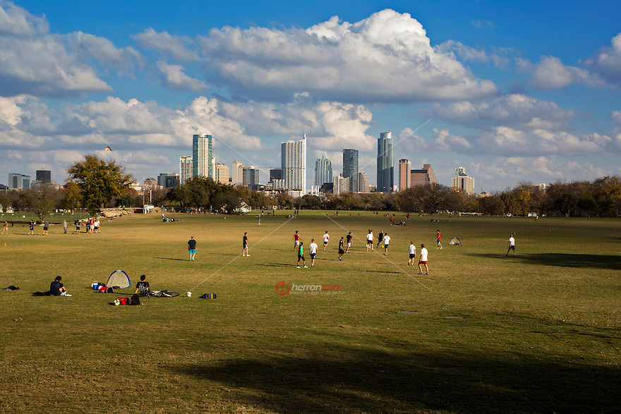 Soccer leagues play soccer during a beautiful sunny day at the Zilker Park soccer and volleyball fields in downtown overlooking the Austin Skyline.
