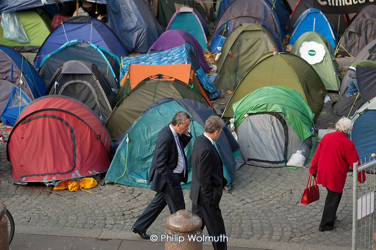 Two businessmen walk through the Occupy London camp, St Paul's Cathedral, on the day after a legal deadline for its removal set by the City of London Corporation.
