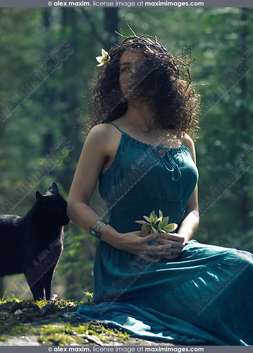 Beautiful young woman wearing a green dress and a wreath made of tree branches in her long dark hair covering part of her face sitting in the nature with a black cat by her side