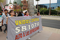 Phoenix, Arizona. April 25, 2012 - Leticia Ramirez (center) and two other  demonstrators hold a sign to show their opposition to SB 1070 as the march arrives to the ICE building on Central Avenue. Ramirez is an undocumented mother of three children who are U.S. citizens. About 500 people protested the controversial law on the same day U.S. Supreme Court justices heard legal arguments on the Arizona vs. United States case. At the end of the march, six activists blocked Central Avenue by sitting in the middle of the street. They all were arrested by the Phoenix Police Department and taken to the Fourth Avenue County Jail. Photo by Eduardo Barraza © 2012