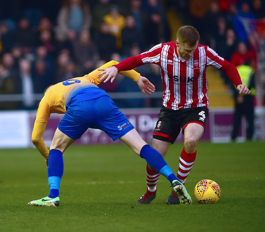 Lincoln City's Michael O'Connor vies for possession with  Mansfield Town's Neal Bishop<br /> <br /> Photographer Andrew Vaughan/CameraSport<br /> <br /> The EFL Sky Bet League Two - Lincoln City v Mansfield Town - Saturday 24th November 2018 - Sincil Bank - Lincoln<br /> <br /> World Copyright © 2018 CameraSport. All rights reserved. 43 Linden Ave. Countesthorpe. Leicester. England. LE8 5PG - Tel: +44 (0) 116 277 4147 - admin@camerasport.com - www.camerasport.com