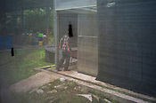 A workers is seen through a netted greenhouse at the pilot project farm involving maggot production in village Kundang, at the outskirts of capital Kuala Lumpur, Malaysia.