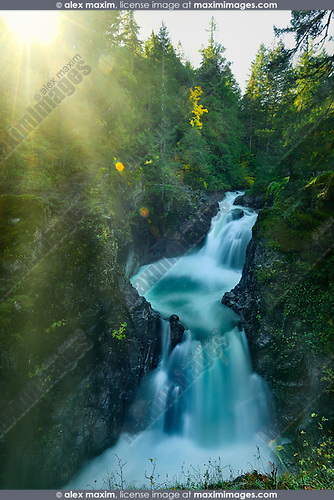 Bright glowing sunshine over beautiful cascade waterfall nature scenery at Little Qualicum Falls Provincial Park, on Little Qualicum River, Vancouver Island, BC, Canada Image © MaximImages, License at https://www.maximimages.com