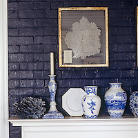 A gold framed coral artwork hangs on the blue brick above elegant vases on the mantle piece.