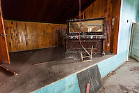 Piano on the stage inside an old abandoned school house near Hemingford, NE