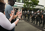 A protestor makes a gesture toward the line of police as tensions escalate during the Solidarity Against Hate rally Sunday August 13, 2017 in Seattle.