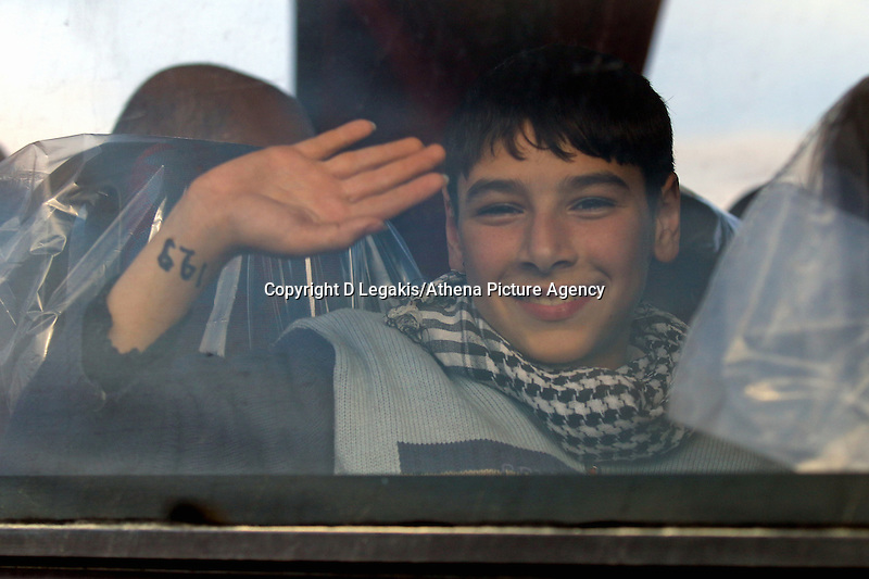 Pictured: A young boy waves from a coach that transferred him and other immigrants to a local gymnasium Thursday 27 November 2014<br /> Re: One of the largest refugee boats in recent months has disembarked refugees in Ierapetra, Crete. The freighter Baris, carrying 700 people thought to be from Syria and Afghanistan, is being towed by a Greek frigate.<br /> Officials and Red Cross volunteers prepared an indoor basketball stadium as interim shelter in the southern Cretan port town of Ierapetra on Wednesday ahead of the migrants' expected arrival.<br /> Greek officials said the Baris, which lost propulsion on Tuesday, was being towed slowly in poor sea conditions and would arrive after nightfall, probably early Thursday.<br /> They said it was unclear which Mediterranean location had been the departure point for the 77-meter (254-foot) vessel, which was sailing under the flag of the Pacific nation of Kiribati.