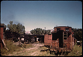 RGS #461 K-27 and caboose in Ridgway yard with roundhouse in background as viewed from sandhouse.<br /> RGS  Ridgway, CO  Taken by Pfeifer, Jack A. - 9/1/1951