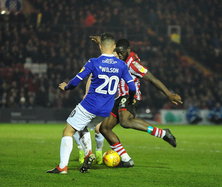 Lincoln City's John Akinde scores his side's first goal to male the score 1-1, under pressure from Exeter City's Kane Wilson<br /> <br /> Photographer Andrew Vaughan/CameraSport<br /> <br /> The EFL Sky Bet League Two - Lincoln City v Exeter City - Tuesday 26th February 2019 - Sincil Bank - Lincoln<br /> <br /> World Copyright © 2019 CameraSport. All rights reserved. 43 Linden Ave. Countesthorpe. Leicester. England. LE8 5PG - Tel: +44 (0) 116 277 4147 - admin@camerasport.com - www.camerasport.com