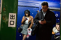 A young woman and man using smart phones in the tourist information office inside an old train car in Hachiko Square, Shibuya, Tokyo, Japan. Friday December 8th 2017