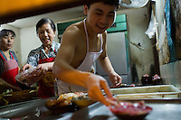 Zhu Zhi Qiang, 19, prepares duck intestine for an order at Gang Shan Zha Zha, a popular streetside hotpot restaurant on Tiyu Road in central Yuzhong distrist, Chongqing, China. Zhu Zhi Qiang, having worked at the restaurant for four years, said &quot;I want to open a shop like this one day.&quot;<br /> <br /> The restaurant sits on the site of a former neighborhood garbage collection point and &quot;zha zha&quot; is local slang for &quot;garbage.&quot; The restaurant has been open for 5 years and recently opened a second location elsewhere in Chongqing. A manager of the restaurant said that they server 60-70 tables every night, with many tables' bills coming to over 1000RMB. The restaurant often has a long wait. The site is well-reviewed on online restaurant sites similar to Yelp and is known for having good flavor, serving fresh food, and being clean.