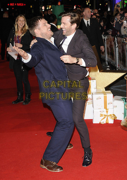 Marc Wootton & David Tennant.The 'Nativity 2: Danger In The Manger' world film premiere, Empire cinema, Leicester Square, London, England..November 13th, 2012.full length blue brown suit funny  arm on shoulder side profile smiling laughing hand arm white shirt  stubble facial hair .CAP/CAN.©Can Nguyen/Capital Pictures.