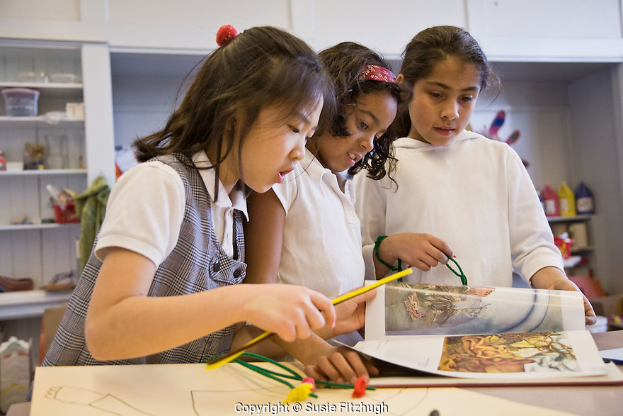 In Lauren Atkinson's Arts Corps class at St. Therese School, girls peruse a book of paintings.