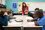 November 15, 2011. Mooresville, NC.. Ms. Thompson, center, a math teacher at East Mooresville Intermediate School, helps a 4th grade class with their math lessons. Much of the class work consists of computer based math tutorials which are turned in electronically allowing the teacher to assist individual students as needed.. The Mooresville school system has become nationally known for being on the cutting edge of using technology as an educational tool. Starting in 3rd grade, each student is issued their own laptop that they will use in class and at home to further their learning.