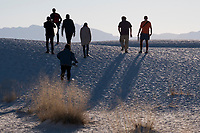 People walk among sand dunes at White Sands National Monument near Alamogordo, New Mexico, USA, on Sat., Dec. 30, 2017.