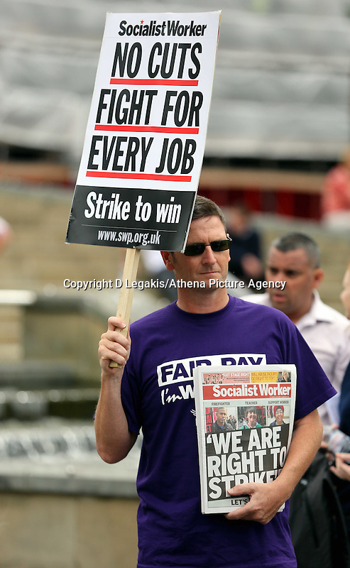 """Swansea, UK. Thursday 10 July 2014<br /> Pictured: A man holding a Socialist Workers placard reading """"No Cuts Fight for Every Job"""" at Castle Square Gardens, Swansea, south Wales.<br /> Re: Strikes are taking place across the UK in a series of disputes with the government over pay, pensions and cuts, with more than a million public sector workers expected to join the action.<br /> Firefighters, librarians and council staff are among those taking part from several trade unions, with rallies taking place across the UK."""