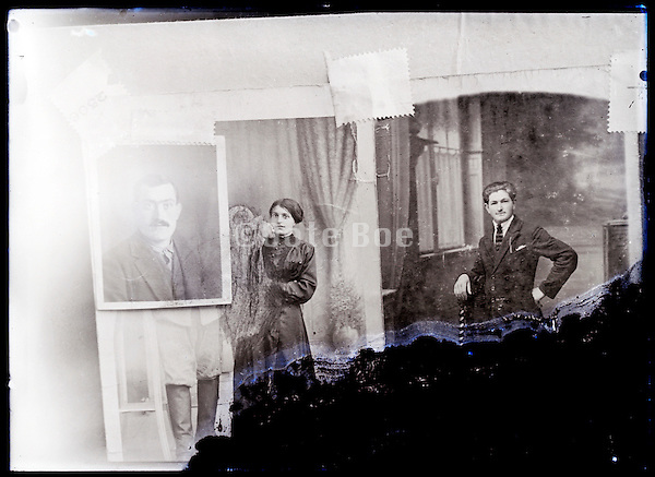 eroding glass plate photo of portrait studio photographs taped to a wall