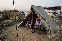 Horse owners smokes in their tent at Pushkar fair ground.  Rajasthan, India.