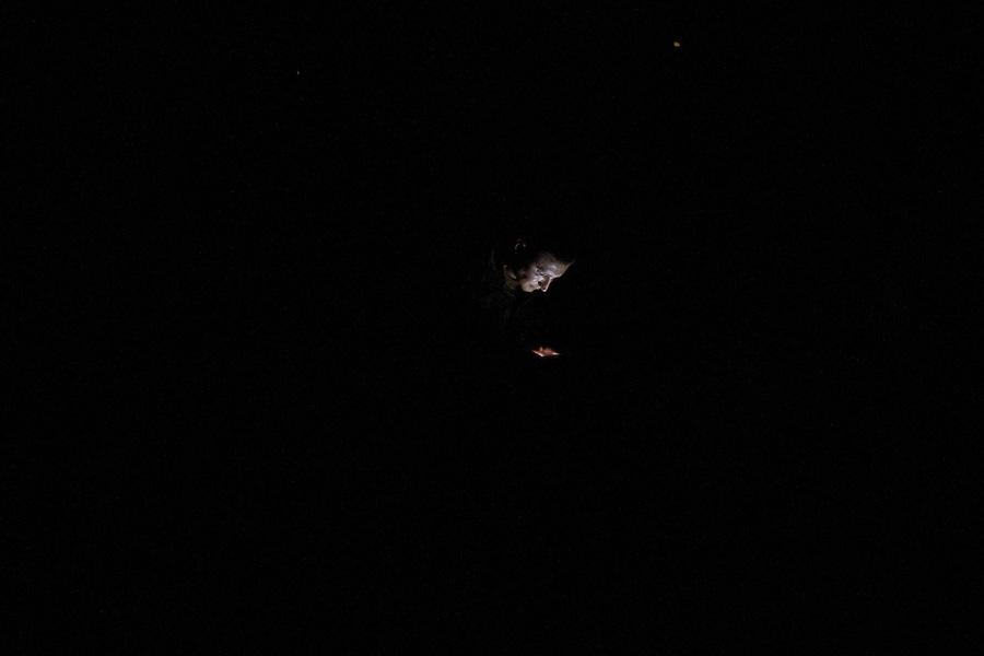 UKRAINE: Frontline de Kalynivka. Un soldat ukrainien regarde son téléphone en dehors de ses casernes pendant la nuit.