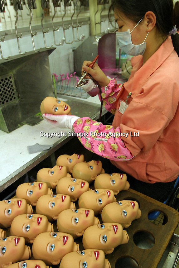 Chinese workers that work at the 'Barbie' division shown painting the 'Cool Crimpin' Styling Head' Barbie at the Mattel (H.K.) Ltd. plant in Guanyao, China. Mattel is the largest toy maker in the world, and manufactures various products from Barbie to Hot Wheels in China..26-FEB-04