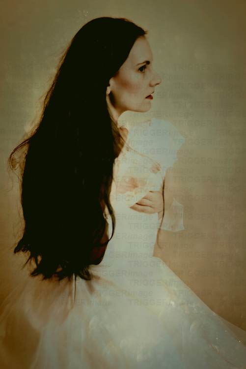 A black haired lady in a white dress with sitting in front of a wall in vintage style
