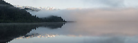 Sunrise fog reflections on Lake Mapourika with Mount Tasman of Southern Alps on horizon, Westland Tai Poutini National Park, West Coast, UNESCO World Heritage Area, New Zealand, NZ