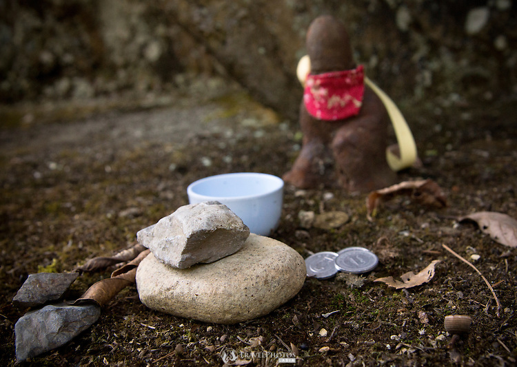 Sake and coin offerings by hikers at a small Buddhist shrine with zen rocks in the Tado mountains.