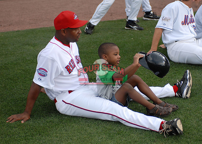 Greenville Drive manager Billy McMillon watches the home run derby action with his son, Jackson, at the 2010 South Atlantic League All-Star Game on Tuesday, June 22, 2010, at Fluor Field at the West End in Greenville, S.C. Photo by: Tom Priddy/Four Seam Images