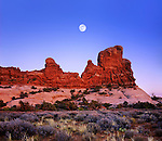 A Deep Blue Evening Sky And Full Moon Rising Over Red Sandstone Rock Forms At Arches National Park, Utah, USA