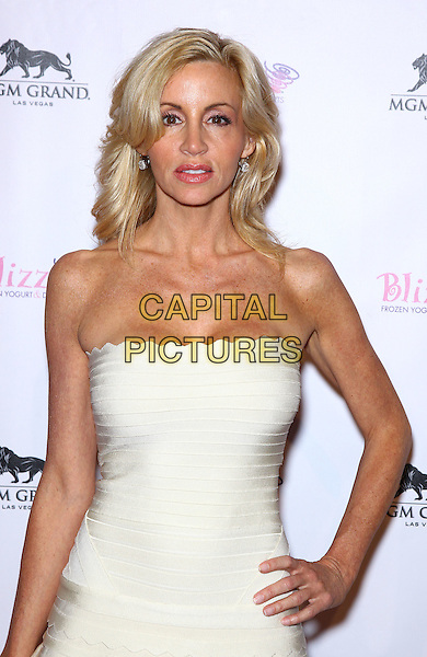 Camille Grammer.The Real Housewives of Beverly Hills walk the red carpet in celebration of the grand opening of the newest Blizz Frozen Yogurt at the MGM Grand  Resort Hotel and Casino, Las Vegas, Nevada, USA, 14th March 2012..half length strapless white dress hand on hip scallop edge trim  .CAP/ADM/MJT.© MJT/AdMedia/Capital Pictures.