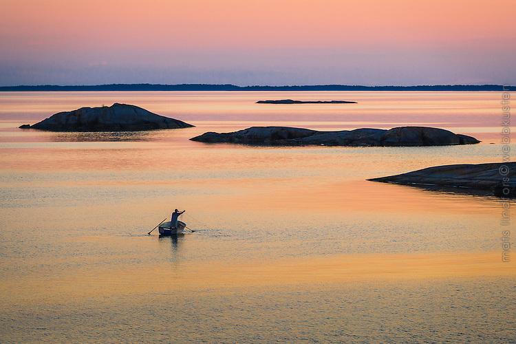 En man lägger nät från sin roddbåt vid Kallskär i Roslagen Stockholms ytterskärgård. / Archipelgo Stockholm Sweden