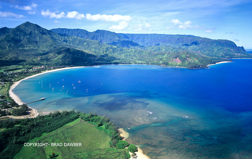 Incredible clear and calm day over Hanalei Bay shot from the air above St. Regis