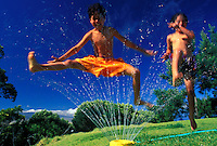two young boys jumping through a water sprinkler having fun