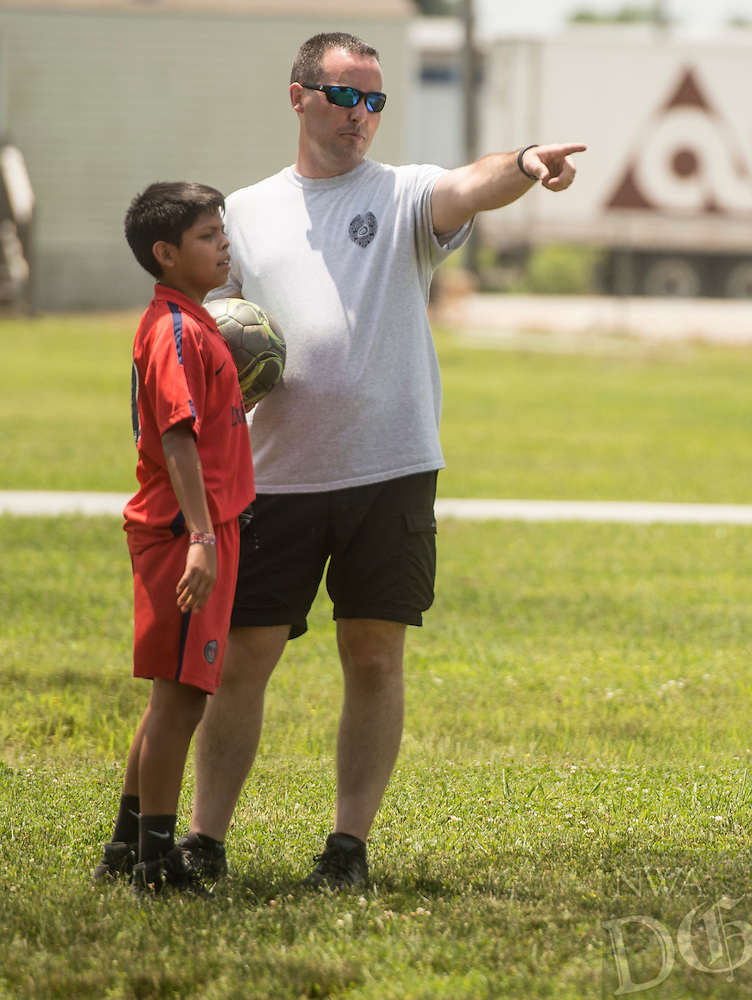 NWA Democrat-Gazette/ANTHONY REYES • @NWATONYR<br /> Juan Barroso, 11, and Garry Jones, with the Springdale police department, discuss strategy Wednesday June 24, 2015 during a soccer game at Jones Elementary School in Springdale. Jones joined other officers for the Sandlot Program where they help mentor the students through play. The officers open up the gymnasium to the children who play and can eat lunch at the school free of charge.