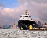 Great Lakes Freighter Canadian Leader tied up at dock with Toronto Ontario Canada North America in the background