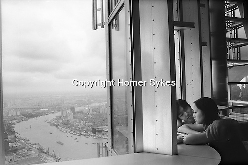 The Peoples Republic of China. Shanghai. 2000. A couple make lovers small talk from the 88th floor, viewing platform of the Jin Mao tower looking down onto the Huangpu river skyline,