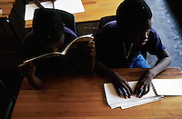 KLIPRIVER, SOUTH AFRICA APRIL 15: Mlungisi Kunene, age 11, (L) and Gcinokwenza Dzanibe, age 8, reads Braille during a class on April 15, 2003 at Sibonile (means: we have seen) School for the Blind in Klipriver, south of Johannesburg, South Africa. A blind woman founded the school in 1994. The school has about 125 students from disadvantaged communities around South Africa. Many of the children have faced rejection from their families and communities, and at Sibonile they have a chance for a good education. .(Photo: Per-Anders Pettersson)..