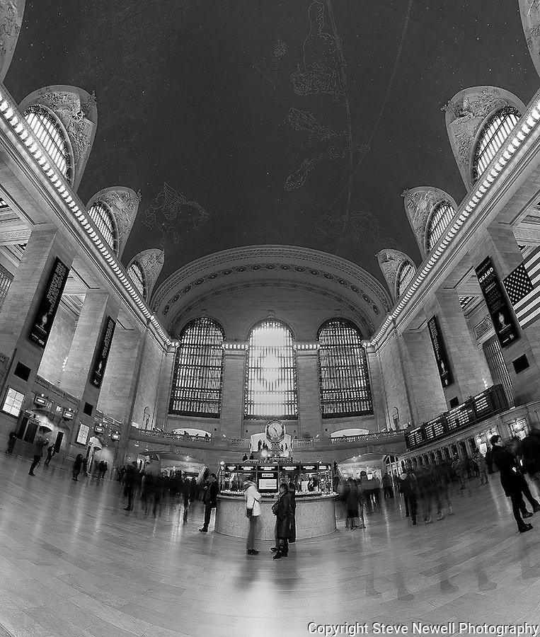 """""""On the Move"""" Black and White Grand Central Terminal Manhattan New York.  I was very fortunate to be able to schedule an hour on the main floor of the Terminal during such a special year. It was the 100th Year Anniversary for the building.  I wanted to try and capture the light coming through the three windows like in the famous classic old photograph taken when the building was first constructed. When I applied for my photography permit(only one photographer allowed on the floor at a time) I was informed that the light to the windows is blocked by the tall buildings that were added after the Terminal's construction. They did however add the large numbers in the windows to celebrate the 100th Anniversary. I have several photographs that have the ceiling with the constellations in view and the incredible chandeliers that hang in surrounding rooms just off the main floor.  I put my camera on the floor and used my remote to fire the shutter to compose the ceiling with the arches of the windows in view. I also have a couple of panoramic photographs that have transparent travelers in motion moving through and cover the entire width of the main floor."""