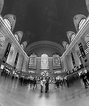 """On the Move"" Black and White Grand Central Terminal Manhattan New York.  I was very fortunate to be able to schedule an hour on the main floor of the Terminal during such a special year. It was the 100th Year Anniversary for the building.  I wanted to try and capture the light coming through the three windows like in the famous classic old photograph taken when the building was first constructed. When I applied for my photography permit(only one photographer allowed on the floor at a time) I was informed that the light to the windows is blocked by the tall buildings that were added after the Terminal's construction. They did however add the large numbers in the windows to celebrate the 100th Anniversary. I have several photographs that have the ceiling with the constellations in view and the incredible chandeliers that hang in surrounding rooms just off the main floor.  I put my camera on the floor and used my remote to fire the shutter to compose the ceiling with the arches of the windows in view. I also have a couple of panoramic photographs that have transparent travelers in motion moving through and cover the entire width of the main floor."