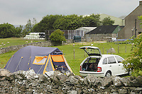 Car and tent in a farm field, Shap, Cumbria.
