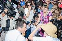 Media surround South Bend mayor and Democratic presidential candidate Pete Buttigieg as he talks to a fairgoer and eats a pork loin on a stick at the Iowa State Fair in Des Moines, Iowa, on Tues., Aug. 13, 2019.
