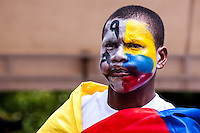 A man with his face painted with colombian flag colors takes part in the rally for a negotiated solution to the conflict and commemoration of the Day of memory of victims in Medellín, Colombia on 09/04/2015